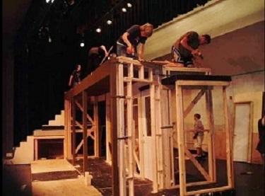 Grips working on building a movie set