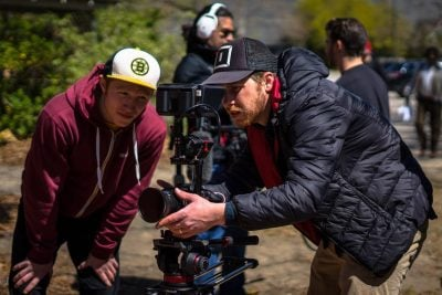 A Film Connection student operating a camera while his mentor advises him.