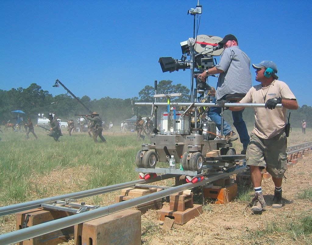Camera man shooting an outdoor war scene using a rail system to move the camera