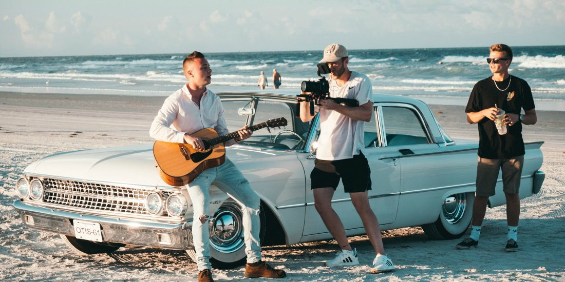 Shooting a music video on the beach with a guitar player and a blue classic car