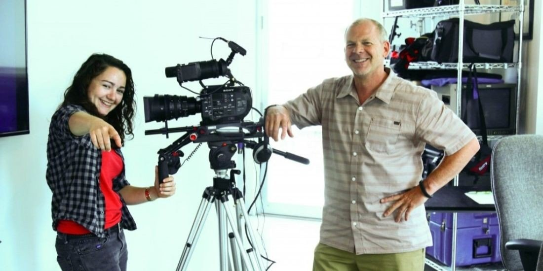Film mentor and female student with camera in production company